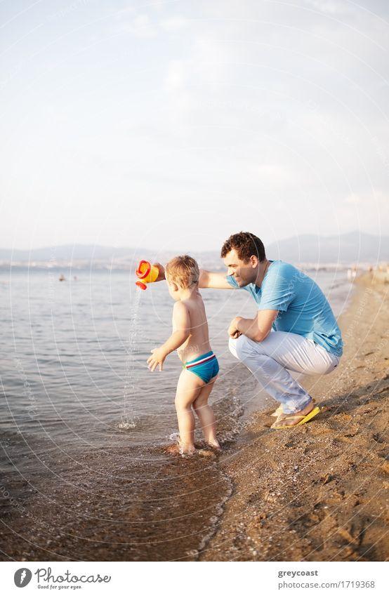 Junger Vater spielt mit seinem Sohn am Strand und kauert sich an den Rand des Wassers, während das Kleinkind fröhlich im seichten Wasser paddelt und mit einer Gießkanne spielt