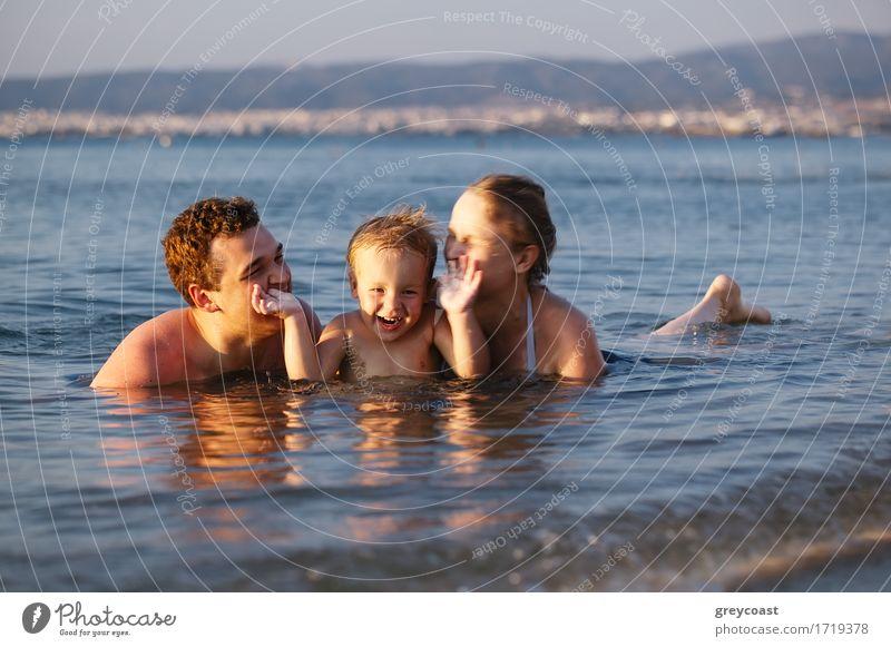 Lachender kleiner Junge flankiert von seinen liebenden Eltern, die gemeinsam im seichten Wasser am Rande des Meeres paddeln Lifestyle Freude Glück schön Leben