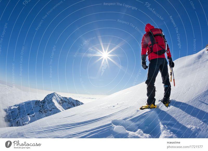 Bergsteiger an der Spitze eines schneebedeckten Berges Abenteuer Expedition Sonne Winter Schnee Berge u. Gebirge Sport Klettern Bergsteigen Erfolg Mann