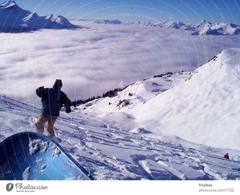 the ride Snowboard Sport Alpen Schnee Snowboarding Snowboarder Tiefschnee Pulverschnee über den Wolken Wolkendecke Tal Schneebedeckte Gipfel abwärts Spuren