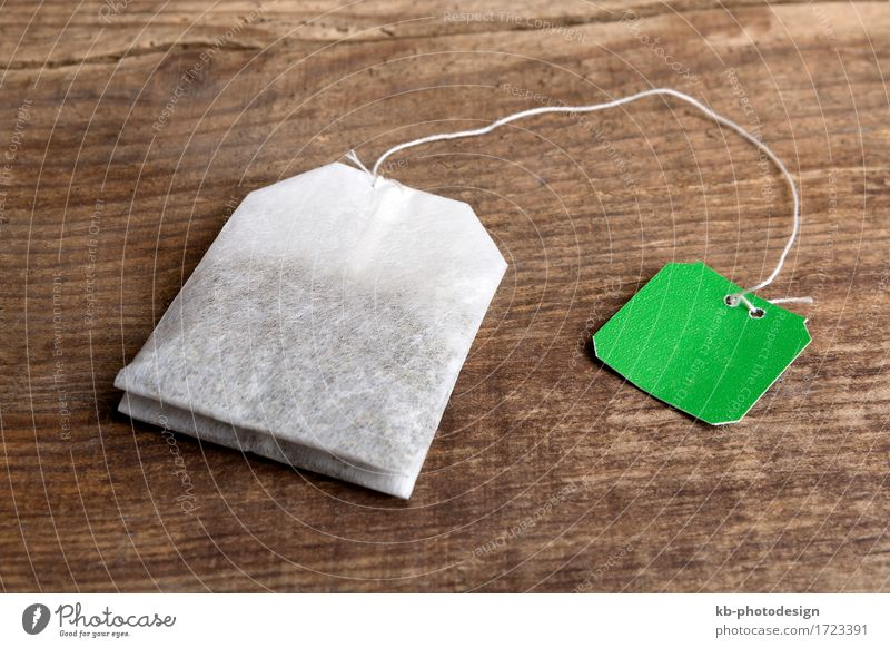 Closeup of green teabag on wooden background Getränk Tee Gesundheit heiß Krankheit mint sage lemon get well healthy sniff cold biologically sick disease