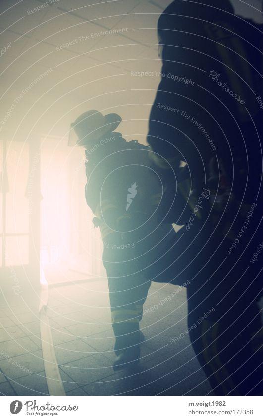 Rettung in letzter Sekunde Gedeckte Farben Innenaufnahme Licht Gegenlicht Mensch Mann Erwachsene 2 Uniform Stiefel Helm Schlauch gehen tragen außergewöhnlich