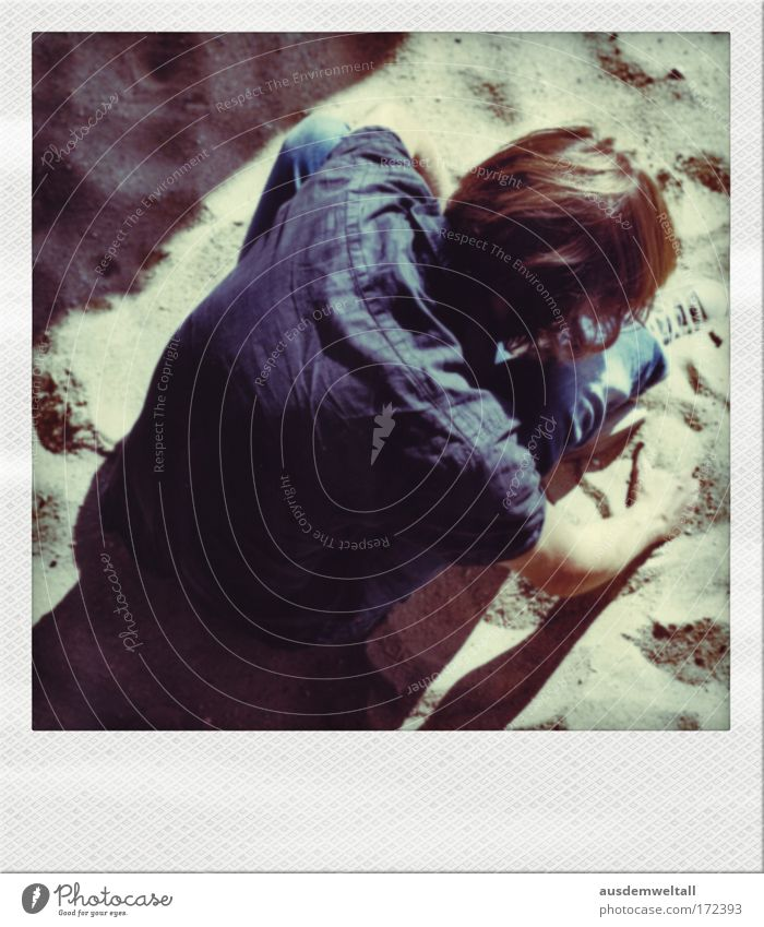 Sandmann Mann maskulin Haare & Frisuren lang braun brünett Hemd blau Jeanshose sitzen beige Schatten Licht hell Sommer Arme Hand Rücken Blick nach unten