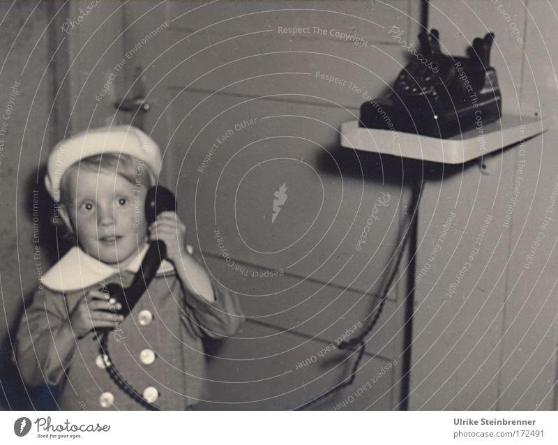 Kleines Mädchen mit Baskenmütze telefoniert Schwarzweißfoto Innenaufnahme Textfreiraum rechts Blitzlichtaufnahme Oberkörper Vorderansicht Blick nach vorn