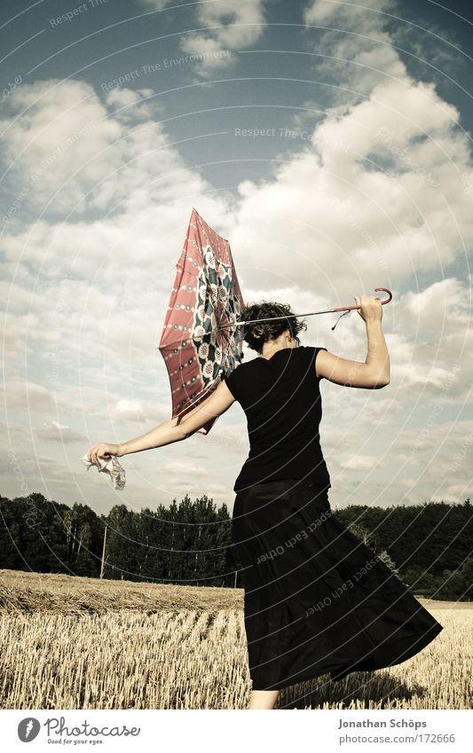 junge Frau in schwarz zeigt mit Schirm nach links vor Wolkenhimmel Lifestyle elegant Stil Freude Glück schön Mensch feminin Junge Frau Jugendliche Leben 1