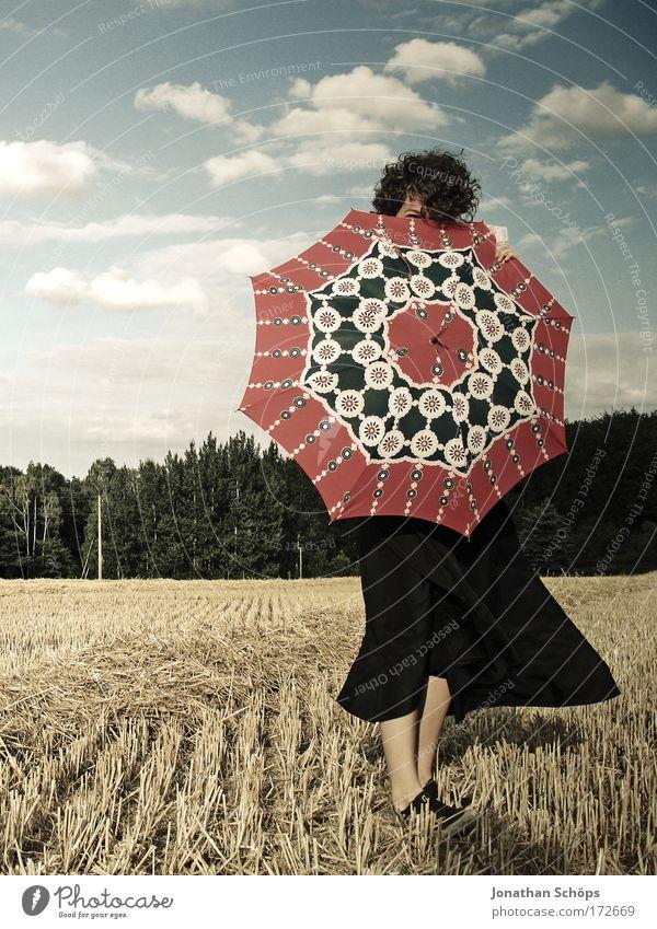 junge Frau in schwarz zeigt mit Schirm nach vorne vor Wolkenhimmel Lifestyle elegant Stil Freude Glück schön Sommer Sommerurlaub Tanzen Mensch feminin