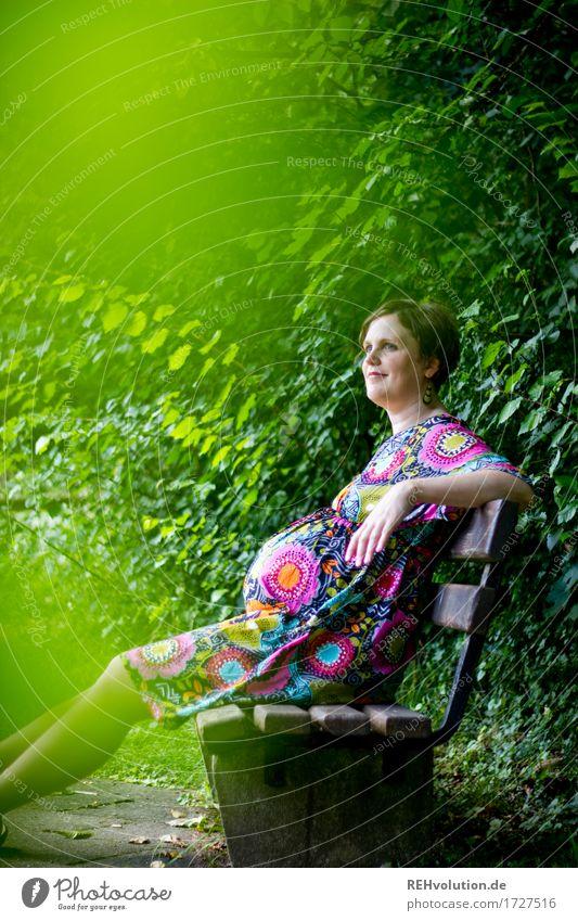 bald ... Mensch feminin Frau Erwachsene Bauch 1 30-45 Jahre Umwelt Natur Pflanze Sträucher Park Wiese Kleid brünett kurzhaarig Bank Erholung Lächeln sitzen