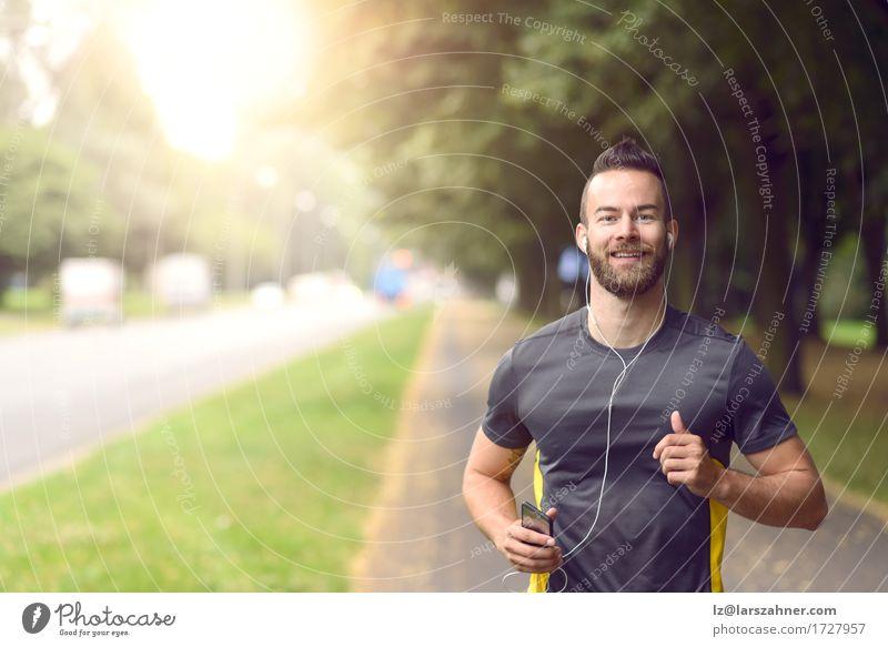 Mann joggt entlang eines von Bäumen gesäumten Bürgersteigs Lifestyle Glück Körper Gesicht Musik Sport Joggen maskulin Erwachsene 1 Mensch 18-30 Jahre