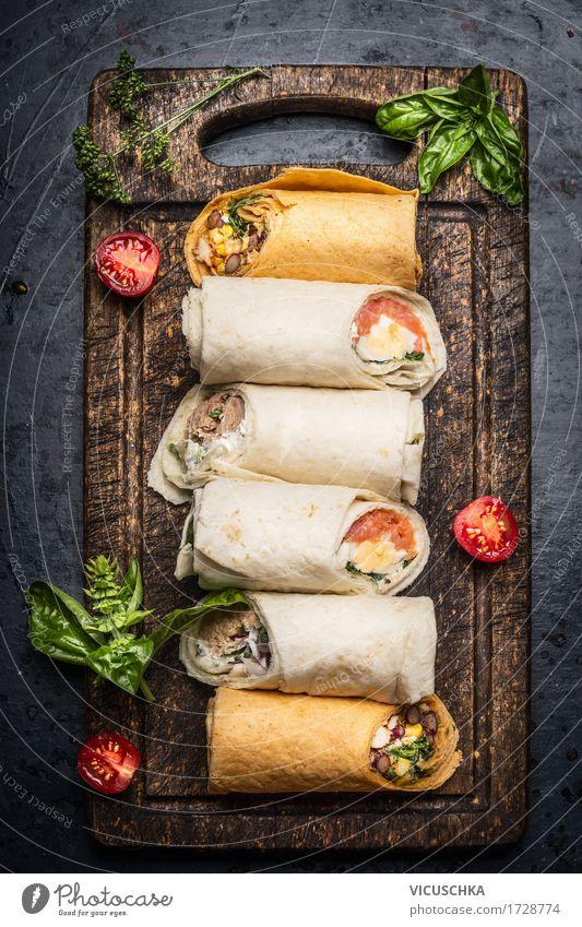 Verschiedene leckere Tortilla Wraps auf rustikalem Schneidebrett Lebensmittel Gemüse Salat Salatbeilage Kräuter & Gewürze Ernährung Mittagessen Abendessen