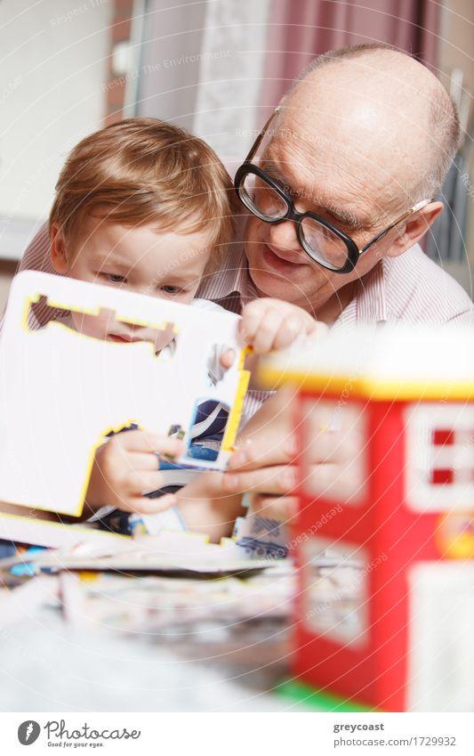 Großvater hilft seinem kleinen Enkel beim Lösen eines Puzzles. Glückliche Familie Zeit Freude Freizeit & Hobby Spielen Kind Mensch Junge Mann Erwachsene