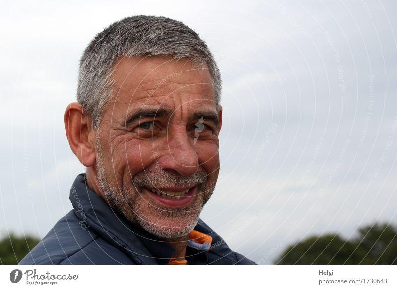 Porträt eines lächelnden Seniors mit grauen Haaren und grauem Bart vor grauem Himmel Mensch maskulin Mann Erwachsene Männlicher Senior Kopf Gesicht 1