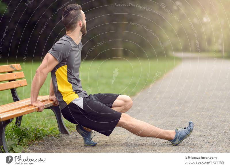 Junger Mann, der in einen Park ausdehnt Mensch Jugendliche 18-30 Jahre Erwachsene Sport Lifestyle maskulin Textfreiraum Körper Aktion Fitness Bank anonym