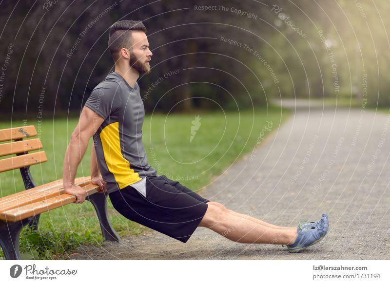 Junger Mann, der in einem Park trainiert Mensch Natur Erwachsene Sport Lifestyle Holz Textfreiraum Körper modern Aktion Fitness Bank sportlich Gleichgewicht