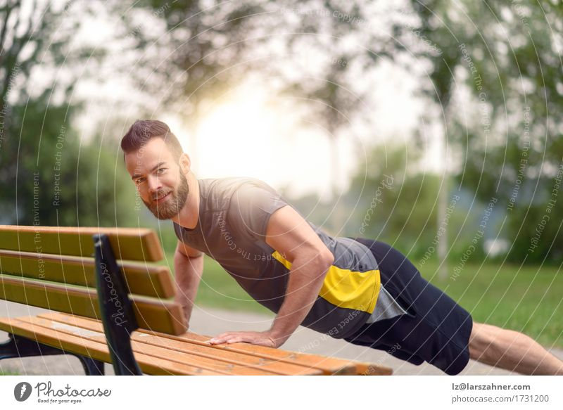 Junger Mann, der StoßUPS in einem Park tut Mensch Jugendliche 18-30 Jahre Gesicht Erwachsene Sport Lifestyle maskulin Textfreiraum Körper Aktion Fitness Bank
