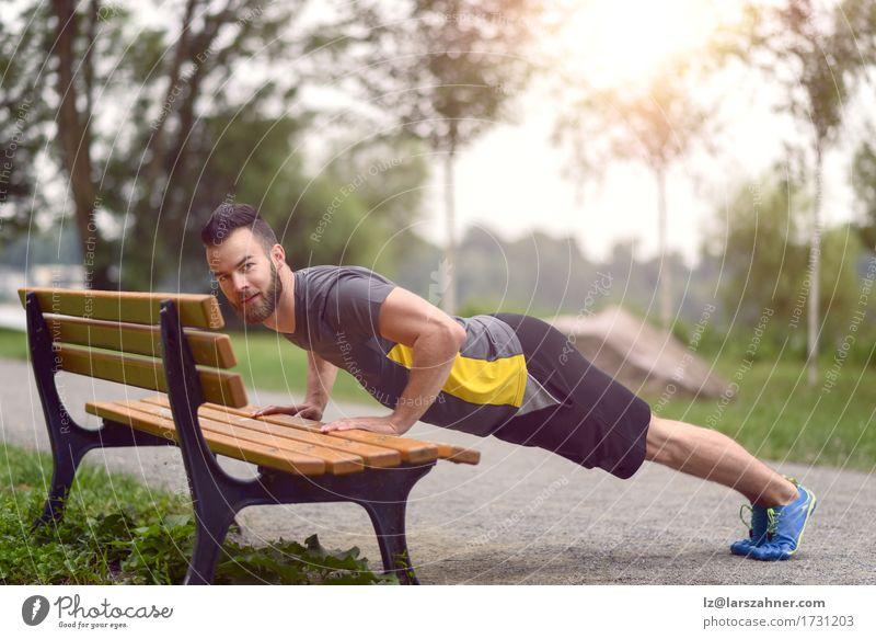 Junger Mann, der StoßUPS in einem Park tut Mensch Jugendliche 18-30 Jahre Gesicht Erwachsene Sport Lifestyle Textfreiraum Körper Aktion Fitness Bank Muskulatur