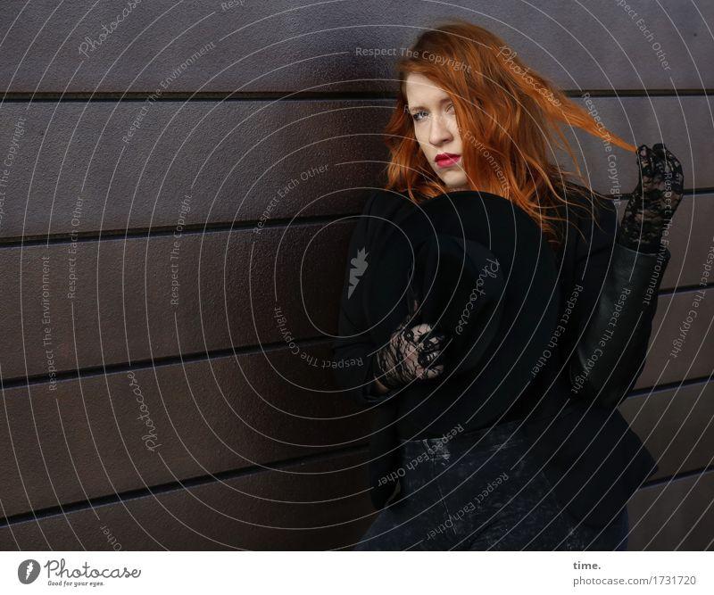 . feminin 1 Mensch Mauer Wand Jacke Handschuhe rothaarig langhaarig beobachten festhalten Blick schön selbstbewußt Coolness Willensstärke Sicherheit Schutz