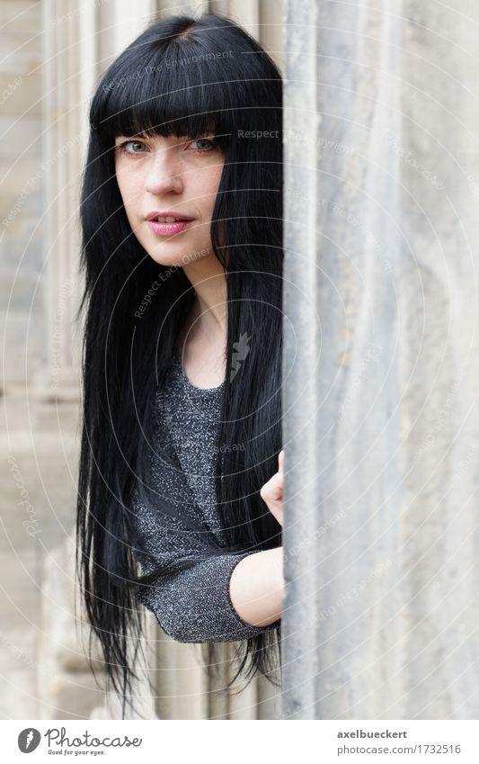 Frau späht hinter einer Säule hervor Lifestyle Mensch feminin Junge Frau Jugendliche Erwachsene 1 18-30 Jahre Gebäude Fenster schwarzhaarig langhaarig Neugier