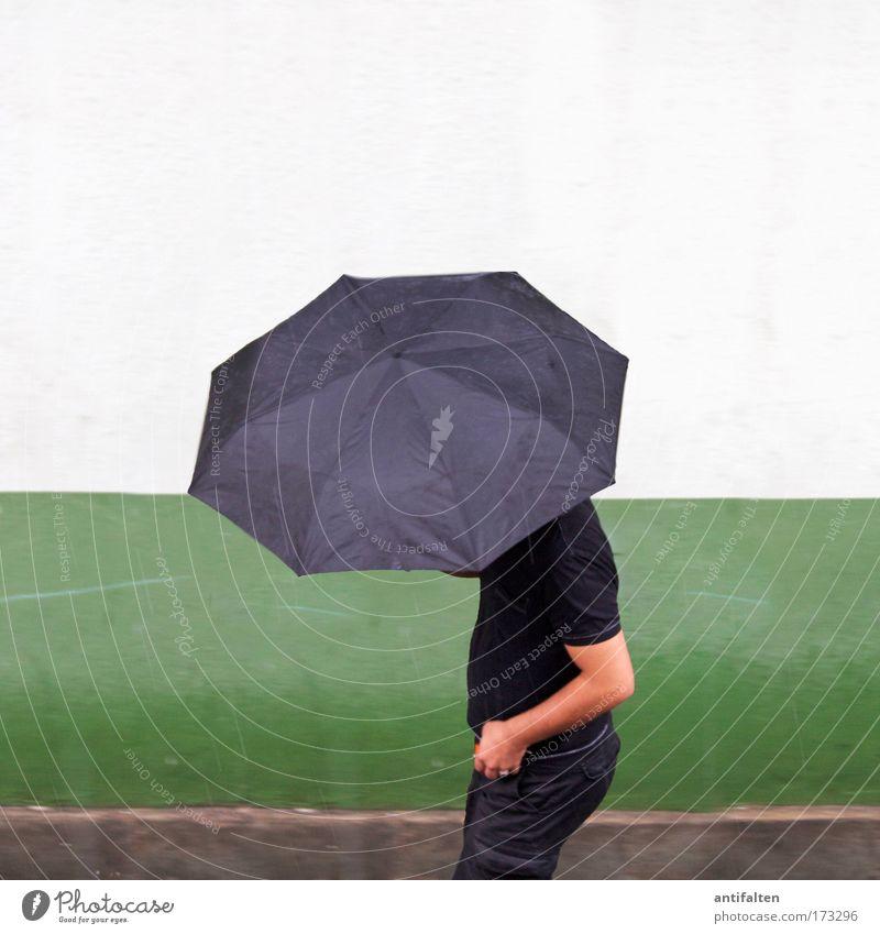Man in black Mensch Mann grün schwarz Haus Erwachsene Wand Mauer gehen Regen Wetter Wind Arme Fassade maskulin Bekleidung