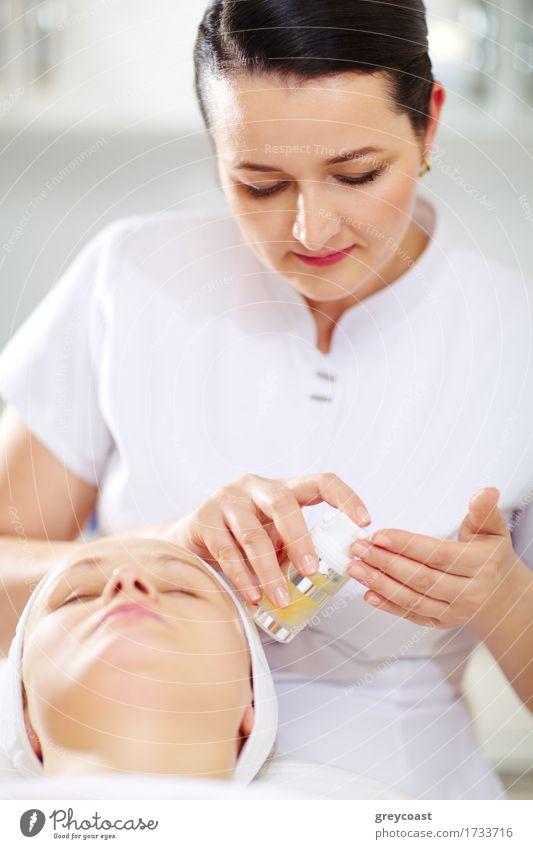 Die Kosmetikerin wird die Gesichtskosmetik während der Behandlung im Schönheitssalon anwenden Haut Gesundheitswesen Spa Arzt Mensch Mädchen Frau Erwachsene