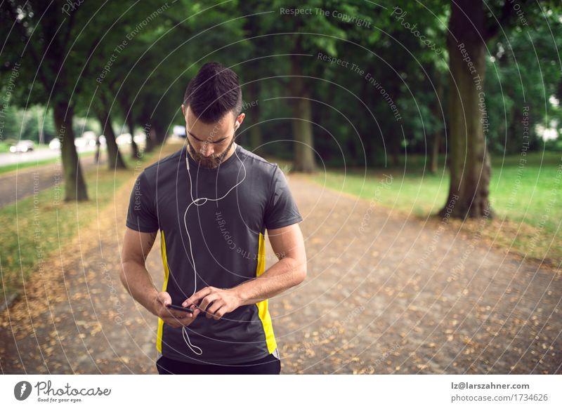 Attraktiver bärtiger Mann, der Musik hört Lifestyle Gesicht lesen Sport Telefon PDA Erwachsene 1 Mensch 18-30 Jahre Jugendliche Park Fitness hören sportlich