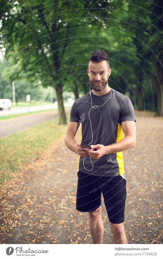 Attraktiver bärtiger Mann, der Musik hört Mensch Jugendliche Sommer 18-30 Jahre Gesicht Erwachsene Sport Lifestyle Park Lächeln Fitness Telefon hören Kopfhörer