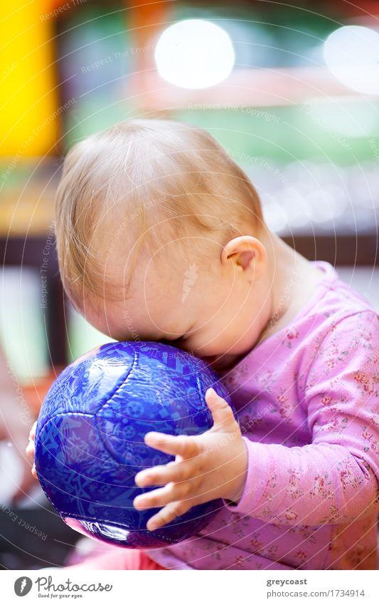 Nettes kleines Baby, das mit einem großen blauen Ball spielt, der mit seinem Gesicht gegen den Ball gedrückt wird, Seitenansicht Freude Spielen Sommer Kind