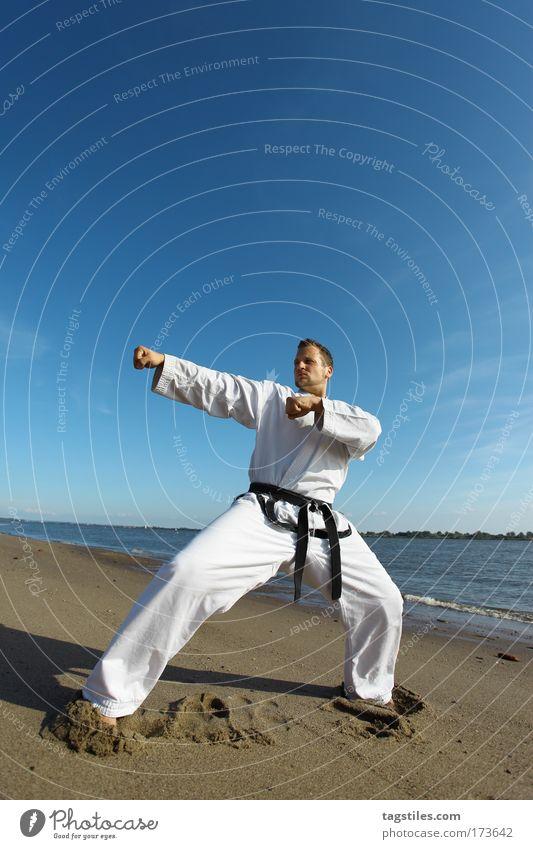 RECHTE GERADE Schlag Züchtigung punch Strand Taekwondo Karate Kämpfer fighter Kampfsport Kampfsportler Farbfoto Textfreiraum oben schwarz Gürtel Kampfanzug