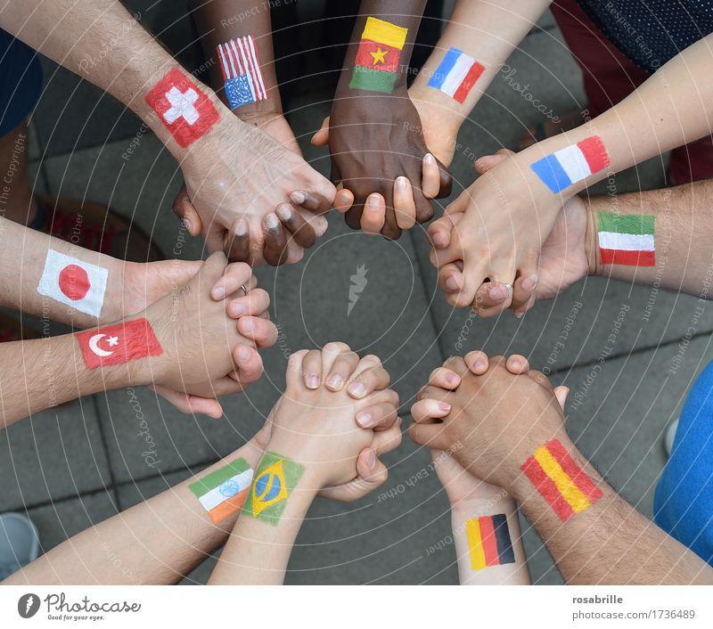 Nationen Hand in Hand - Menschen verschiedener Nationalitäten mit aufgemalten Flaggen halten sich an den Händen als Zeichen für Frieden und Solidarität