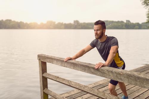 Junger Mann, der das Ausdehnen von Übungen tut Mensch Jugendliche Sommer 18-30 Jahre Gesicht Erwachsene Wärme Sport Lifestyle Holz See maskulin Textfreiraum