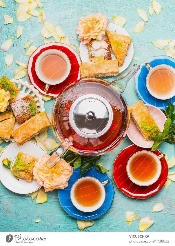 Teepause mit Tassen , Blumen , Kuchen und Teekanne Lebensmittel Dessert Frühstück Mittagessen Getränk Heißgetränk Geschirr Teller Stil Design Häusliches Leben