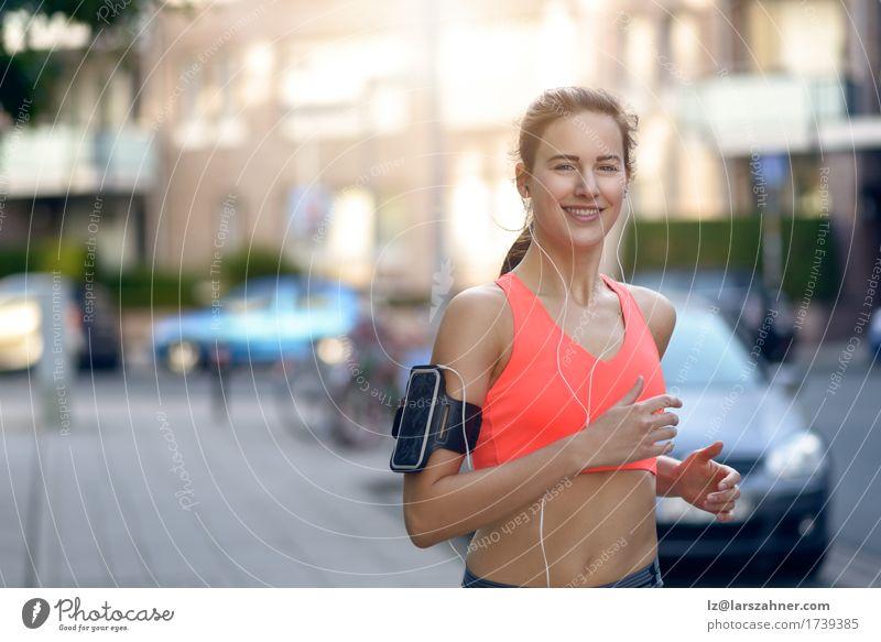 Geeignete junge Frau, die entlang einer städtischen Straße rüttelt Junge Frau Jugendliche Erwachsene 1 Mensch 18-30 Jahre Gesundheit Konzept Lifestyle rennen