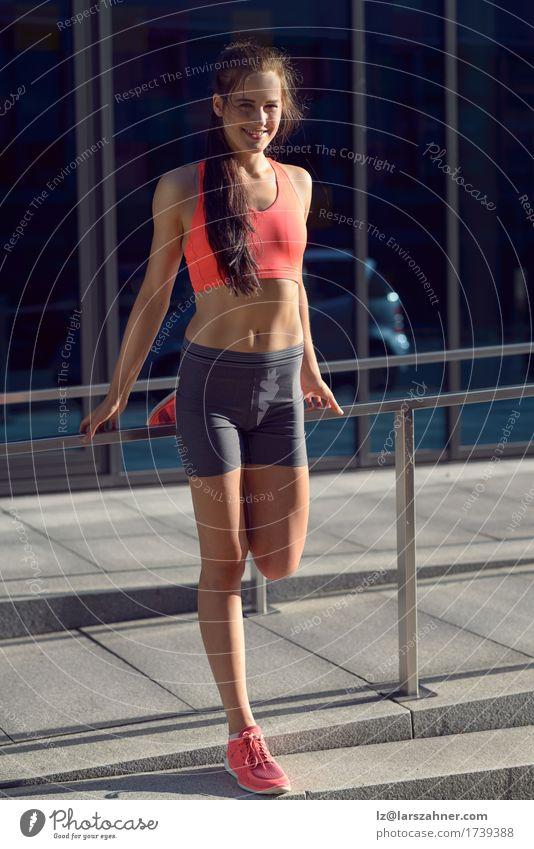 Geeignete junge Frau, die Übungen ausdehnend tut feminin Junge Frau Jugendliche Erwachsene 1 Mensch 18-30 Jahre Glück Lächeln Dehnübung Aktion Fitness Stadt