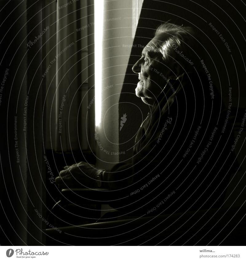 Alte Mann sitzt im Rollstuhl am Fenster im Dunkel alter Mann Senior Mensch Alter Porträt Erinnerung Einsamkeit Ruhestand Pflegeheim pflegebedürftig