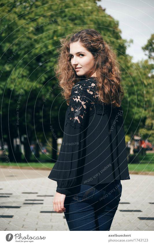 junge Frau schaut über Schulter Lifestyle schön Mensch feminin Junge Frau Jugendliche Erwachsene 1 18-30 Jahre Park Platz Jeanshose brünett langhaarig Locken