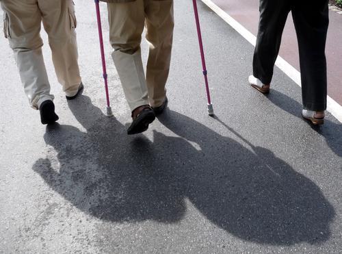 Beine von gehenden Senioren mit Stützen im Sonnenlicht mit Schatten auf einer Straße Farbfoto Gedeckte Farben Außenaufnahme Detailaufnahme Tag Licht Kontrast