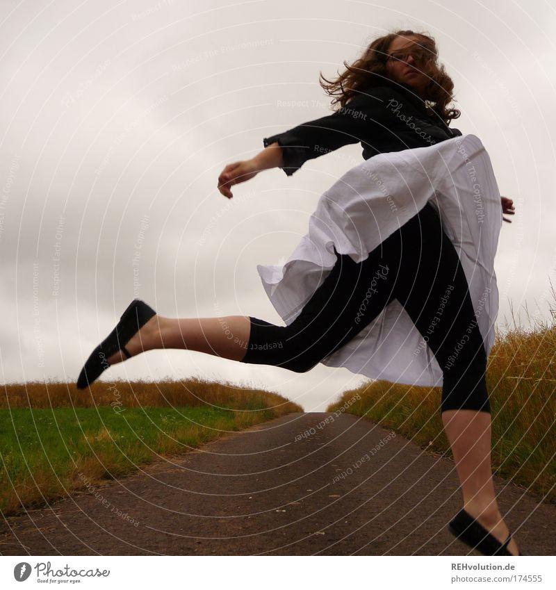 Frau springt auf einer Straße Farbfoto Außenaufnahme Ganzkörperaufnahme Freude Mensch feminin Junge Frau Jugendliche 1 18-30 Jahre Erwachsene Landschaft Wiese