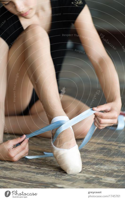 Mädchen mit langen Beinen binden ihre Ballettschuhe auf dem Boden elegant schön Studium Mensch 1 13-18 Jahre Jugendliche Tänzer Balletttänzer Krawatte Schuhe