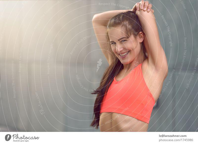 Geeignete athletische junge Frau, die Übungen ausdehnend tut Mensch Jugendliche Mädchen 18-30 Jahre Gesicht Erwachsene Sport Lifestyle Glück grau Textfreiraum