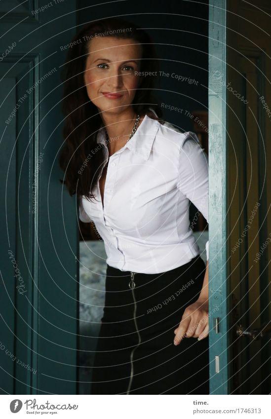 . Häusliches Leben Tür Türrahmen feminin 1 Mensch Hemd Rock brünett langhaarig beobachten festhalten Lächeln Blick stehen Freundlichkeit schön Zufriedenheit