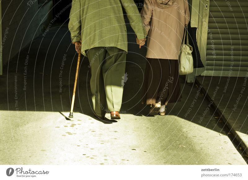Paar Ehe Partnerschaft Romantik Liebe Zuneigung Zusammensein Hand in Hand Mann Frau alt Senior Ruhestand Tunnel dunkel Durchgang Stock Gehhilfe Spazierstock
