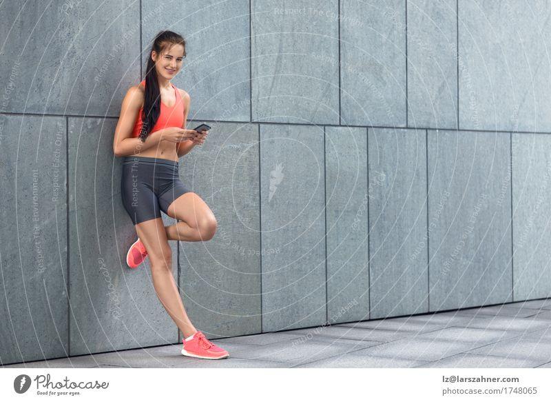 Sportliche junge Frau, die ihr Mobile überprüft Gesicht Sommer Telefon PDA Erwachsene 1 Mensch 18-30 Jahre Jugendliche Wärme brünett Fitness Lächeln stehen