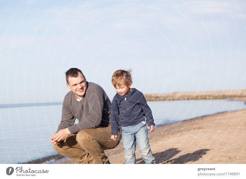 Lächelnder Vater mit seinem kleinen Sohn am Strand, der sich lächelnd in den Sand hockt, während der Junge neben ihm steht Freude Glück Meer Erwachsene