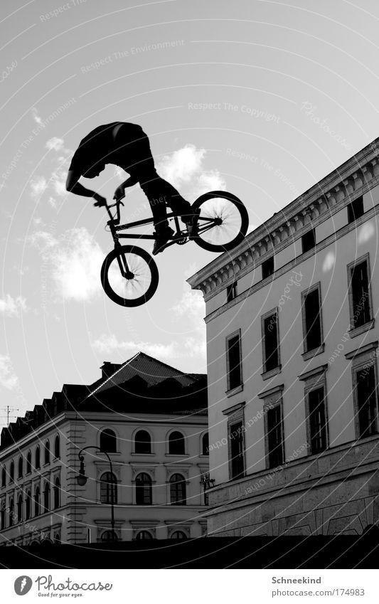 Überflieger Schwarzweißfoto Außenaufnahme Tag Licht Schatten Sonnenlicht Starke Tiefenschärfe Froschperspektive Ganzkörperaufnahme Wegsehen Sport Fahrrad