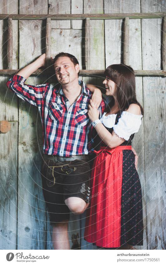 Junges Paar in Tracht vor Holzhütte Lifestyle Tourismus Haus Oktoberfest Jahrmarkt Mensch maskulin feminin Junge Frau Jugendliche Junger Mann Eltern Erwachsene