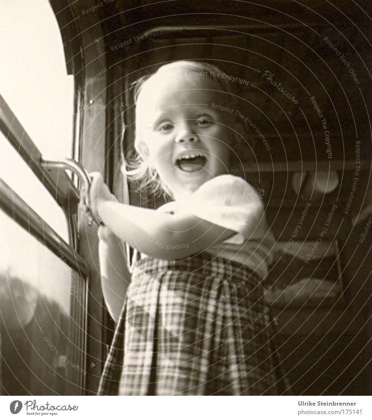 Kleines lachendes Mädchen steht am offenen Zugfenster Schwarzweißfoto Innenaufnahme Tag Oberkörper Blick in die Kamera Mensch Kind 1 3-8 Jahre Kindheit