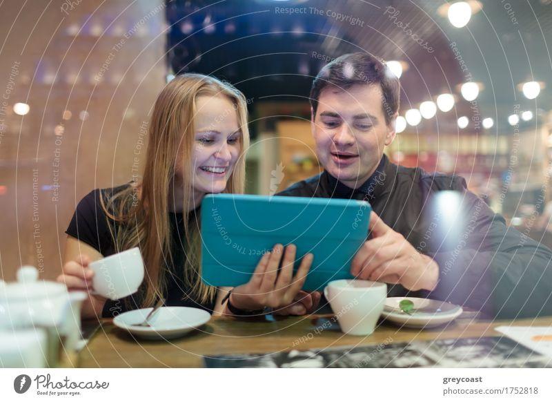 Glücklicher junger Mann und Frau trinken Kaffee beim Blick auf Tablet Tee Restaurant Sitzung Computer Junge Frau Jugendliche Junger Mann Geschwister Paar 2