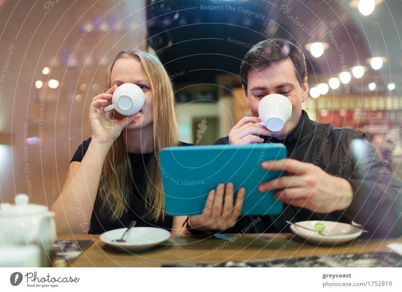 Mann und Frau trinken Kaffee Mensch Jugendliche Junge Frau Junger Mann 18-30 Jahre Erwachsene Gefühle Paar blond Computer Restaurant Café Sitzung brünett Tee