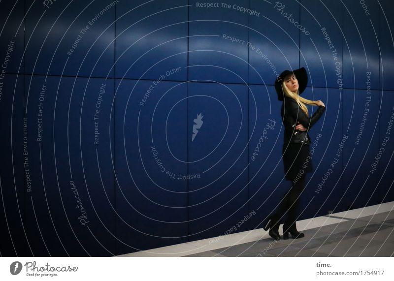 . feminin Frau Erwachsene 1 Mensch Mauer Wand Wege & Pfade Tunnel Bahnsteig Mantel Stiefel Hut blond langhaarig beobachten festhalten Blick stehen warten dunkel