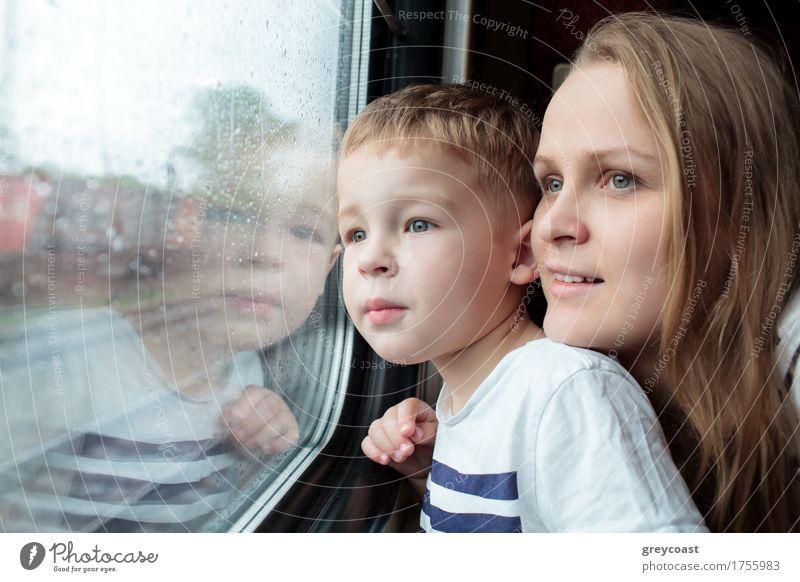 Mutter und Sohn schauen durch ein Zugfenster, während sie eine Tagesreise genießen, wobei sich das Gesicht des kleinen Jungen im Glas spiegelt