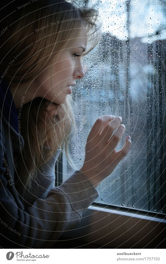Frau, die durch Fenster mit Regentropfen schaut Mensch feminin Junge Frau Jugendliche Erwachsene 1 18-30 Jahre Herbst Winter Wetter schlechtes Wetter blond